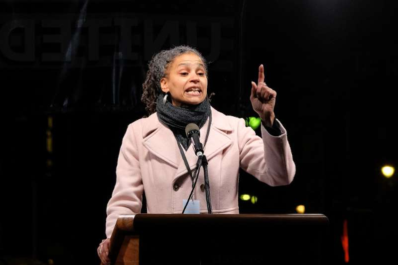 Maya Wiley wearing a suit and tie standing in front of a stage: Maya Wiley, a 2021 New York City mayoral candidate, speaks during the We Stand United NYC event in New York City on January 19, 2017.