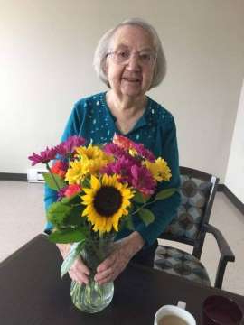 a woman sitting at a table with a vase of flowers: Florence Kines, 92, was transferred to several different hospitals and transported five times by ambulance, and once by air, to get medical attention after breaking a hip in December.