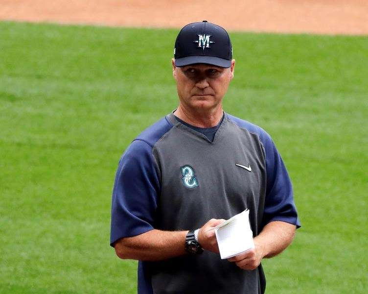 Scott Servais standing on a baseball field