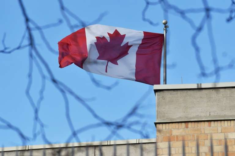 a close up of a flag: The Canadian flag flies over the Canadian embassy in Beijing: Canadian MPs have voted overwhelmingly to label China's treatment of its Uighur minority a 'genocide'