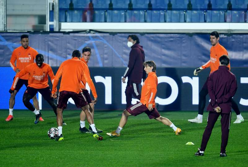 a group of people playing football on a field: Champions League - Real Madrid Training