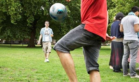 a group of people playing frisbee in a park: Grassroots football return: When can you play