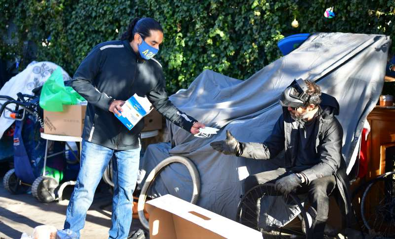 a group of people riding on the back of a bicycle: A member of the Los Angeles Homeless Services Authority offering a face mask to a homeless man on December 3, 2020 in Venice, California. State lawmakers have approved a COVID-19 relief bill that would see 5.7 million California residents each receive a stimulus payment of $600.