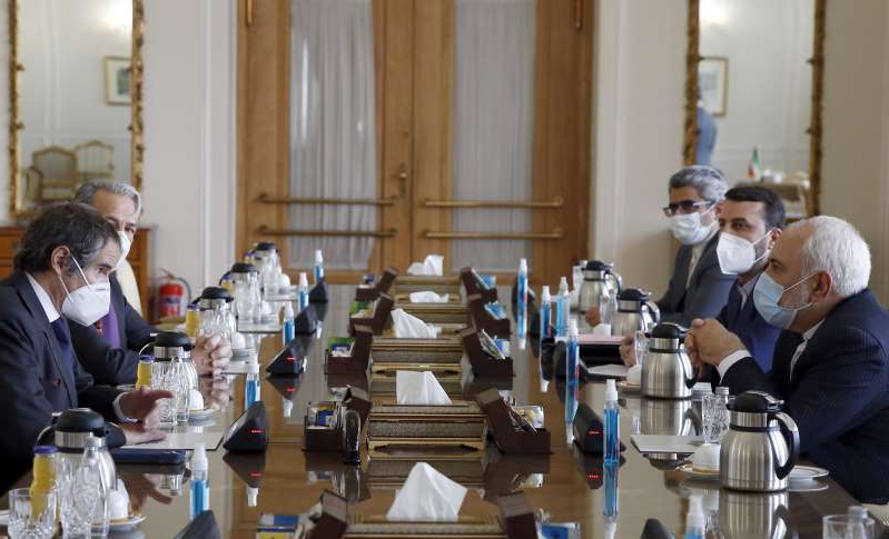 a group of people sitting at a table: Iran' Foreign Minister Mohammad Javad Zarif (L) meets with the director general of the International Atomic Energy Agency (IAEA), Rafael Grossi (R), in Tehran on February 21. The two sides reached a