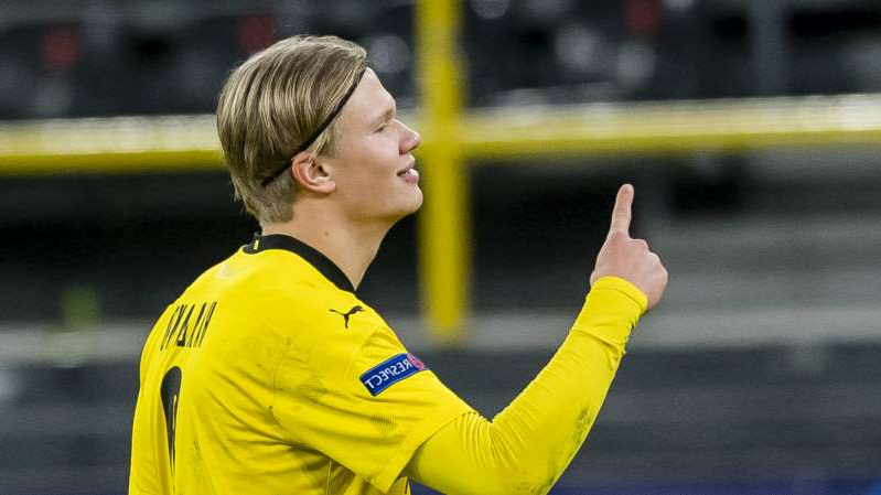 a hand holding a football ball: Borussia Dortmund striker Erling Haaland has been linked with Barcelona