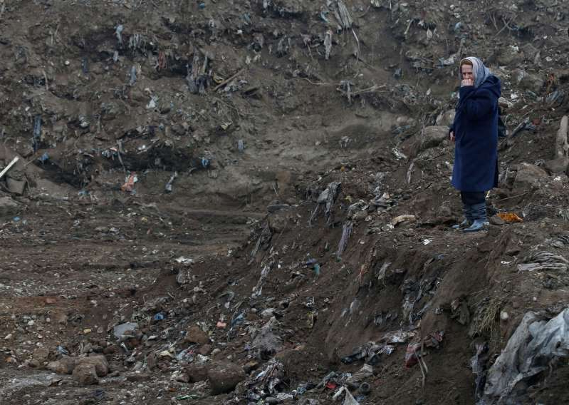 a man that is standing in the dirt: Nura Begovic, a Bosnian woman from Srebrenica, looks at a mass grave in the village of Kozluk, near the eastern town of Zvornik, Bosnia and Herzegovina [File: Amel Emric/AP Photo]