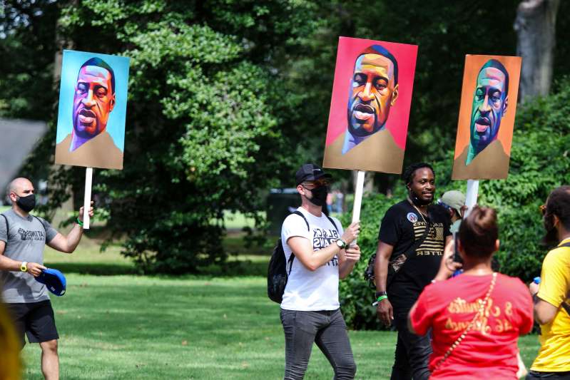 Protesters hold signs of George Floyd during the Commitment March at the Lincoln Memorial on August 28, 2020 in Washington, DC.