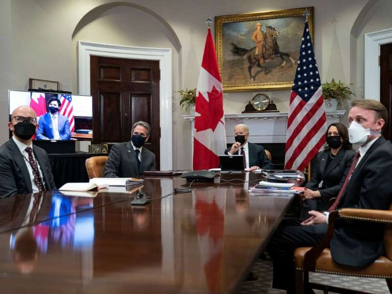 a group of people sitting at a table: President Joe Biden holds a virtual bilateral meeting with Canadian Prime Minister Justin Trudeau, in the Roosevelt Room of the White House, Feb. 23, 2021, in Washington.