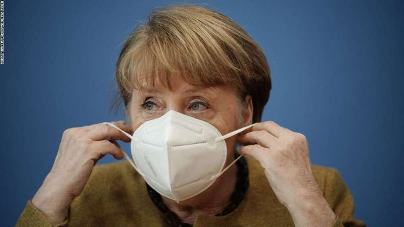 a close up of a boy: German Chancellor Angela Merkel puts on her face mask after giving a press conference on the Covid-19 situation in Germany at the house of the Federal Press Conference (Bundespressekonferenz), on January 21, 2021 in Berlin. (Photo by Michael Kappeler / POOL / AFP) (Photo by MICHAEL KAPPELER/POOL/AFP via Getty Images)