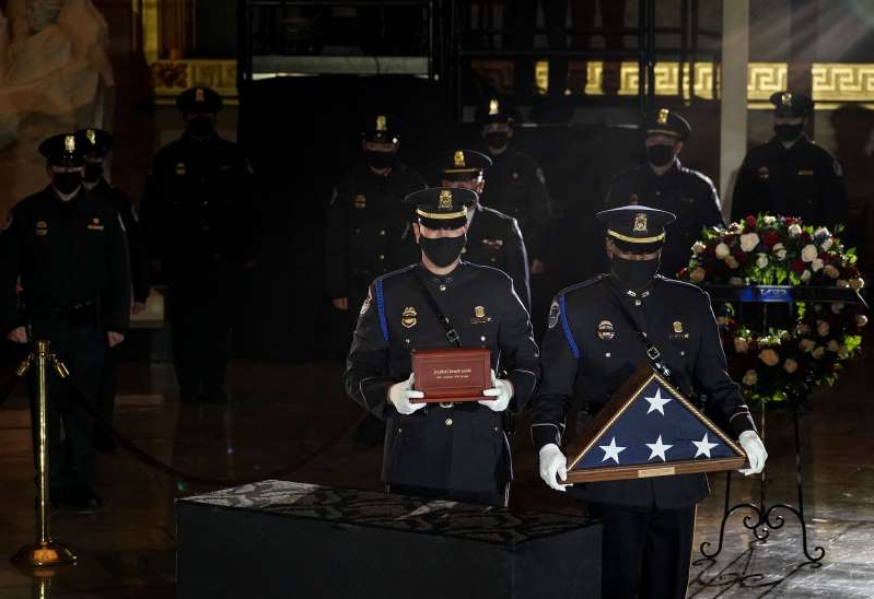 a group of people standing in a room: U.S. Capitol Police Officers carry the urn holding the remains of fellow officer Brian Sicknick and a U.S. flag to lie in honor in the Capitol Rotunda in Washington, February 2, 2021.