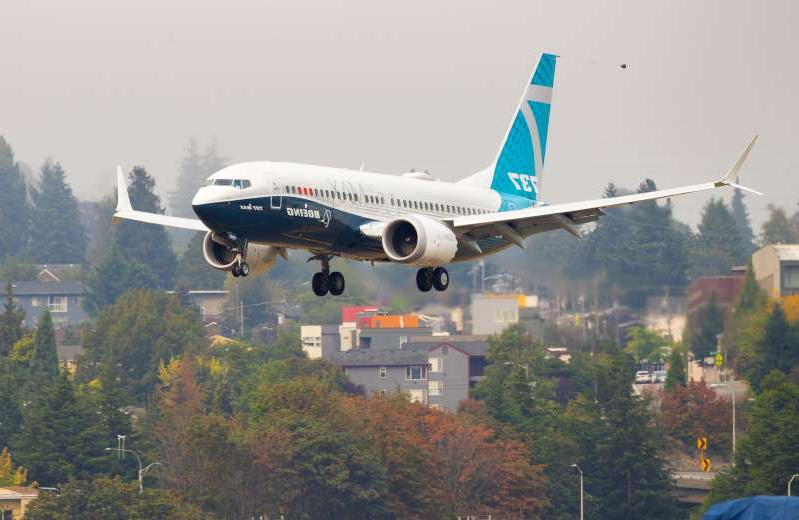 a large air plane flying in the sky: Boeing's 737 MAX aircraft re-entered US commercial service in December after the Federal Aviation Administration approved changes the planemaker made to an automated flight-control system implicated in the crashes in Indonesia and Ethiopia [File: Mike Siegel/Pool via Reuters]