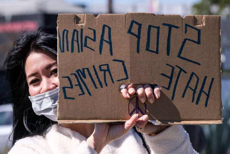 A demonstrator wearing a face mask and holding a sign takes part in a rally to raise awareness of anti-Asian violence, near Chinatown in Los Angeles, California, on February 20, 2021