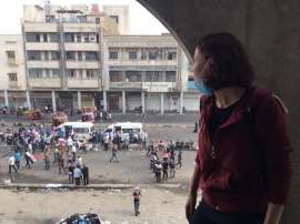 a group of people standing in front of a building: Sally Mars, a 24-year-old Iraqi woman who joined protests against the government, wants to see her country's oil wealth used to help its people, not lost to corruption [Courtesy: Sally Mars]