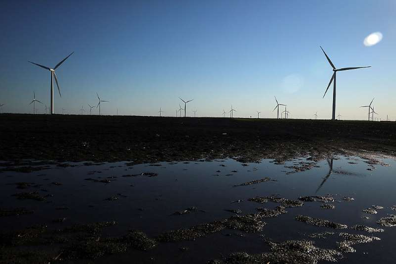 a large body of water: Wind turbines are viewed at a wind farm on March 27, 2015 in Taft, Texas