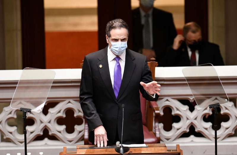 a man wearing a suit and tie: New York Governor Andrew Cuomo speaks to members of New York state's Electoral College before voting for President and Vice President in the Assembly Chamber at the state Capitol in Albany, New York on December 14, 2020. Billboards calling for Cuomo's impeachment have appeared in Albany.