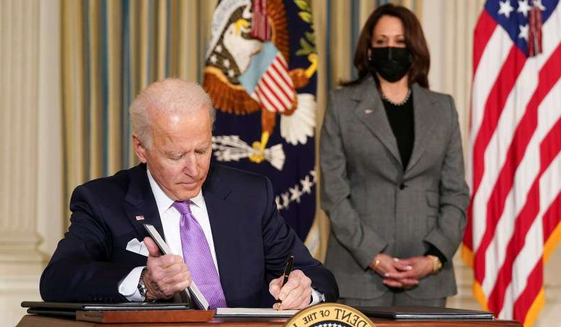 Joe Biden wearing a suit and tie: Vice President Kamala Harris watches as President Joe Biden signs executive orders on his racial equity agenda at the White House, January 26, 2021.