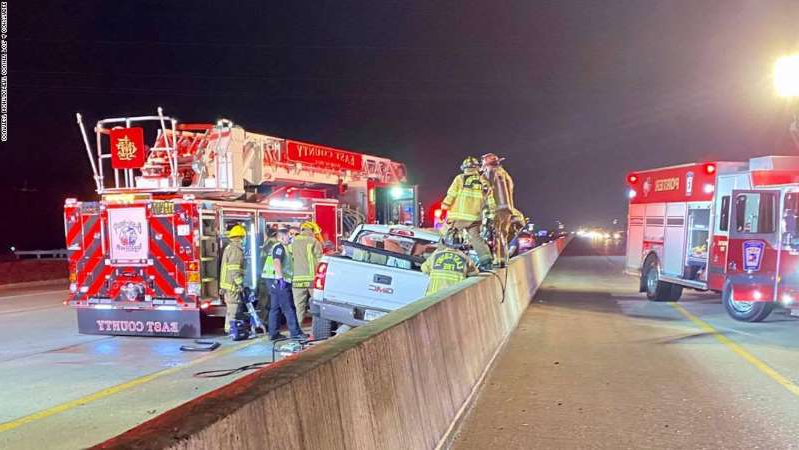 a group of people riding on the back of a truck: Firefighters examine a vehicle involved in a fatal accident on Interstate 59 in Texas on Thursday, February 25.