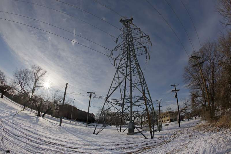 a man riding skis down a snow covered slope: Electric provider Griddy has been banned as of Friday from operating in the Texas market due to missed payments, and customers will be transitioned to other providers. A transmission tower supports power lines after a snow storm on February 16, 2021 in Fort Worth, Texas.