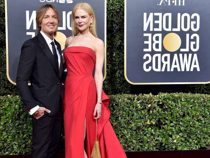 Nicole Kidman, Keith Urban holding a sign posing for the camera