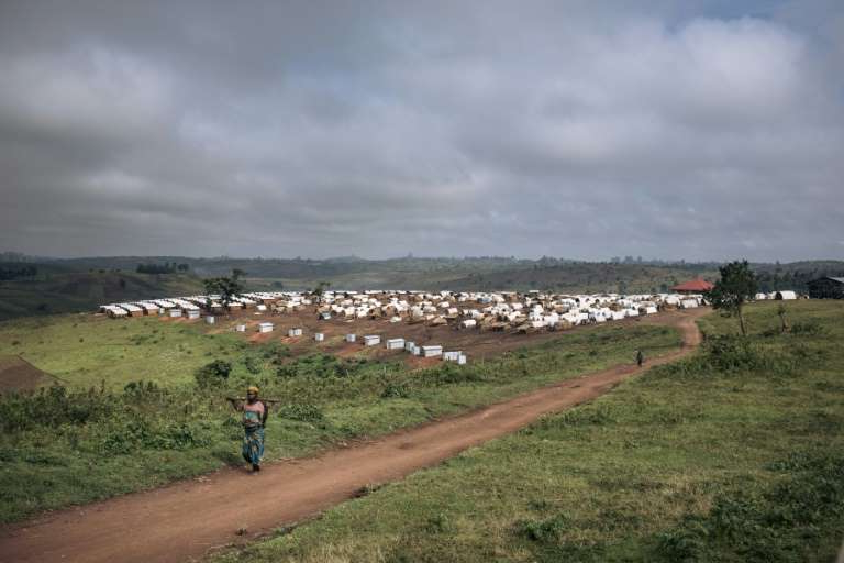 a group of people walking on a grassy hill: Ituri province's villages and camps for displaced people are regularly targetted by armed militia