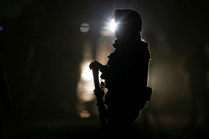 a man that is standing in the dark: A soldier guards the area where eleven people were killed when unidentified gunmen riding in a truck opened fire in Tonala