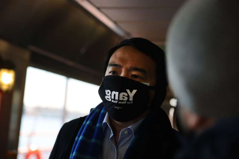 a person wearing a mask: Andrew Yang, who is currently leading the contenders in his Democratic primary run for mayor of New York City, rides the Staten Island Ferry during a campaign stop to the borough on February 26 in New York City