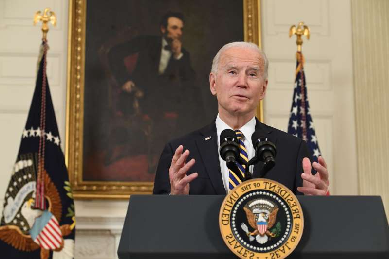 Joe Biden wearing a suit and tie: President Joe Biden speaks before signing an executive order in the State Dining Room of the White House in Washington, D.C.