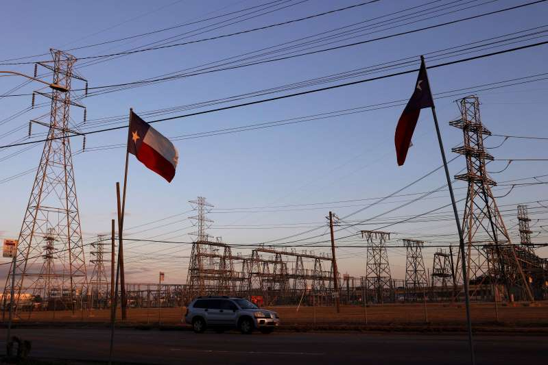 Texas flags fly near an electrical substation in Houston. Millions of Texans lost their power when a winter storm hit the state and knocked out unprepared power plants.