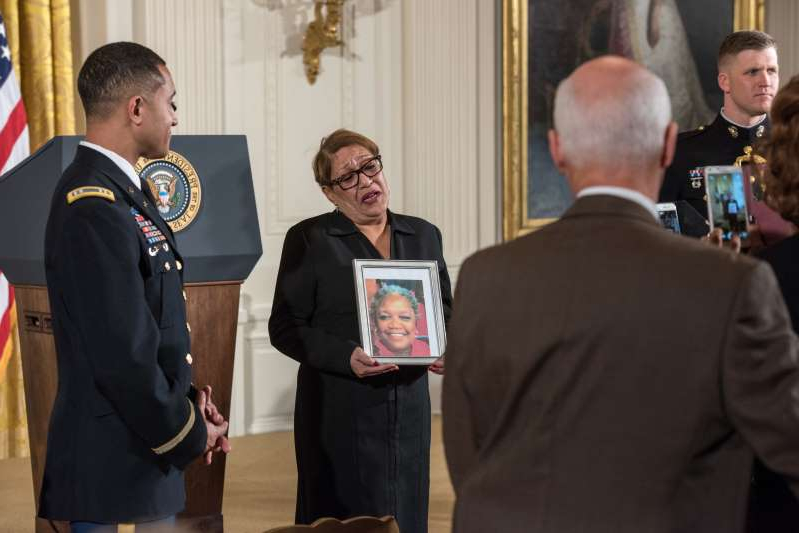 a group of people standing next to a man in a suit and tie: Rev. Sharon Risher, holds up a photo of her mother Ethel Lance, who died at 70, as she has her photo taken prior to U.S. President Barack Obama giving remarks in the East Room of the White House about his efforts to increase federal gun control Jan. 5, 2016 in Washington, DC.