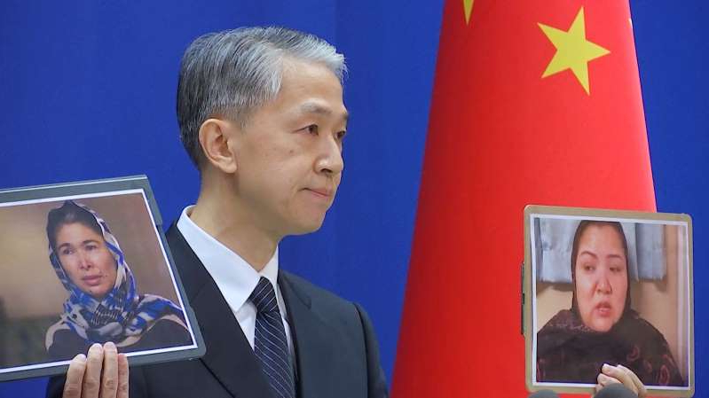 a young boy wearing a suit and tie: Chinese Foreign Ministry spokesman Wang Wenbin holds pictures while speaking during a news conference in Beijing