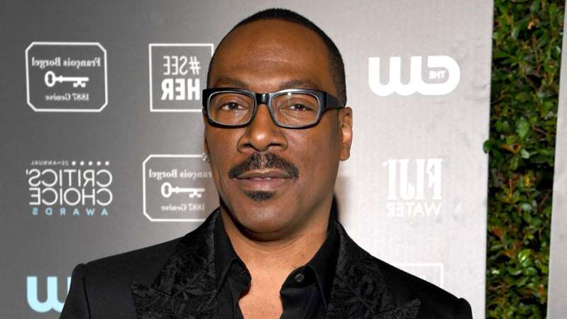 a man wearing glasses posing for the camera: Eddie Murphy