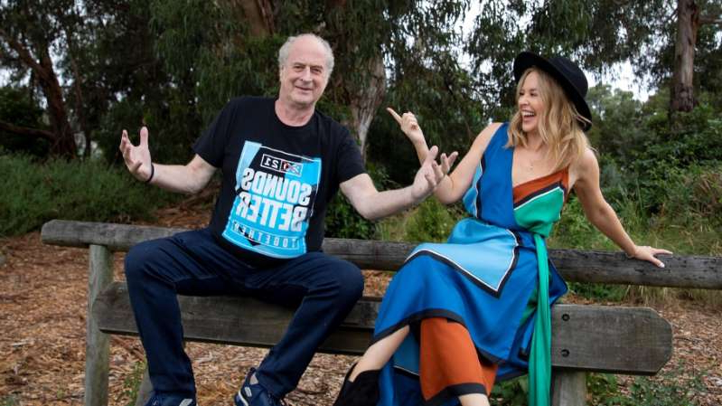 Michael Gudinski et al. sitting on a bench posing for the camera