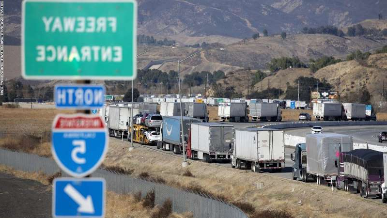 a sign on the side of a mountain: Vehicles back up on the northbound Interstate 5 as seen from the Hasley Canyon Road exit in Castaic on January 26, 2021. A series of winter storms in California closed several major highways, including parts of I-5.