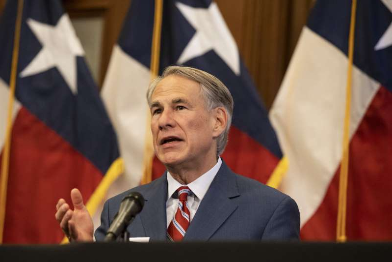 Greg Abbott wearing a suit and tie: Texas Governor Greg Abbott at a press conference at the Texas State Capitol in Austin on Monday, May 18, 2020. On March 2, 2021, Abbott said he would lift the mask mandate and allow businesses to open to 100 percent capacity.