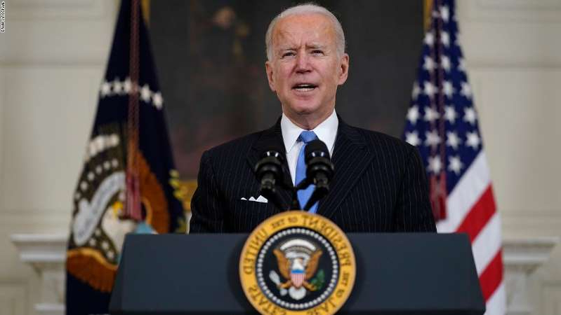 Joe Biden wearing a suit and tie: President Joe Biden speaks about efforts to combat COVID-19, in the State Dining Room of the White House, Tuesday, March 2, 2021, in Washington. (AP Photo/Evan Vucci)