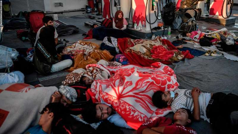 a group of people sleeping on the bed: Homeless migrants and refugees sleep at a gas station after a fire destroyed Greece's largest Moria refugee camp on the island of Lesbos, early on September 11, 2020. - Thousands of asylum seekers on the Greek island of Lesbos languished on roadsides, homeless and hungry after the country's largest camp burned down, with local officials stonewalling government efforts to create new temporary shelters. (Photo by LOUISA GOULIAMAKI / AFP) (Photo by LOUISA GOULIAMAKI/AFP via Getty Images)