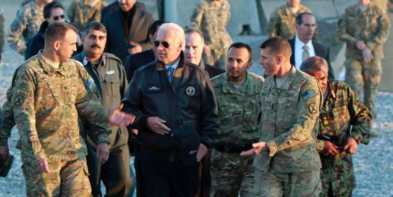 a group of people standing next to a man in a military uniform: Then-Vice President Joe Biden meets with U.S. troops in Maidan Wardak province January 11, 2011. Omar Sobhani/Reuters