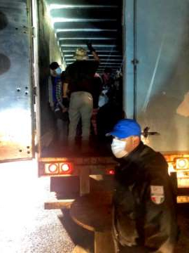 a group of people standing in front of a window: Police found 201 migrants jammed into a trailer in Mexico's southern Chiapas state Wednesday, the day after 13 people were killed in a crash involving an SUV filled with migrants in Imperial County. (Mexico National Institute of Migration)