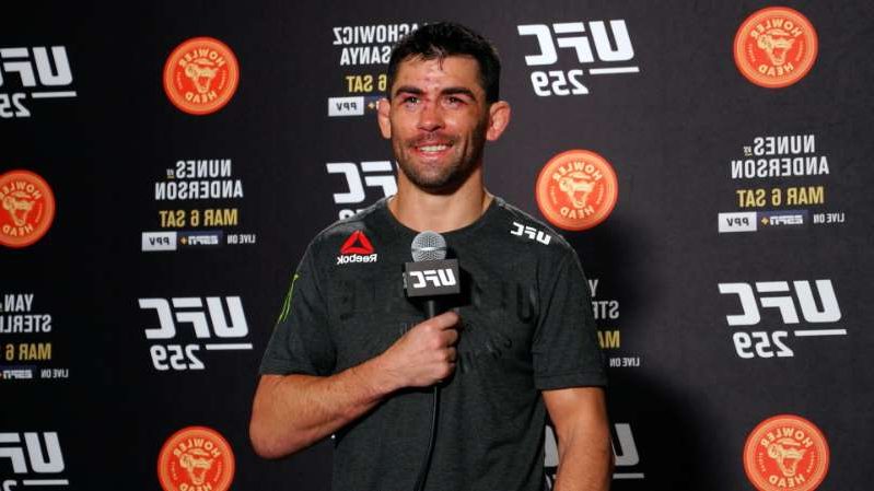 Dominick Cruz holding a sign posing for the camera