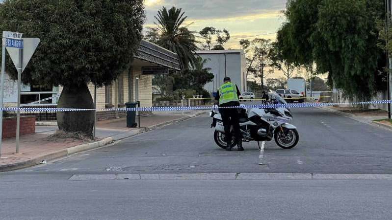 a person riding a motorcycle down a street: Police have cordoned off an area around Brady Street in Viriginia. (ABC News: Mahalia Carter)