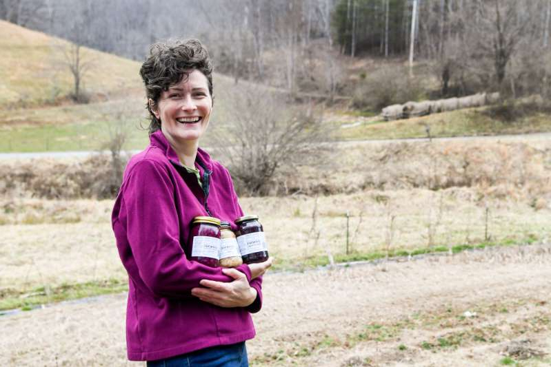 a little girl standing in a field: Meg Chamberlin holds jars of her fermented produce next to her field in Marshall February 26, 2021.