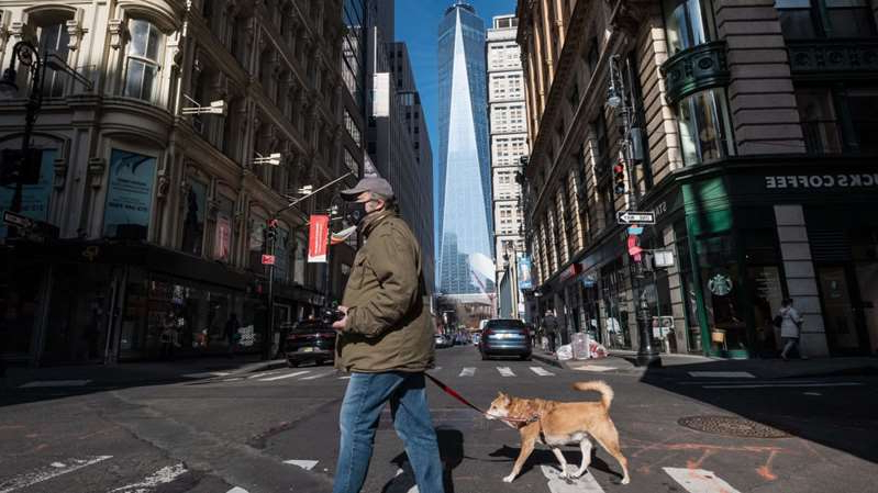 a man and a woman walking down a city street: Angela Weiss/AFP via Getty