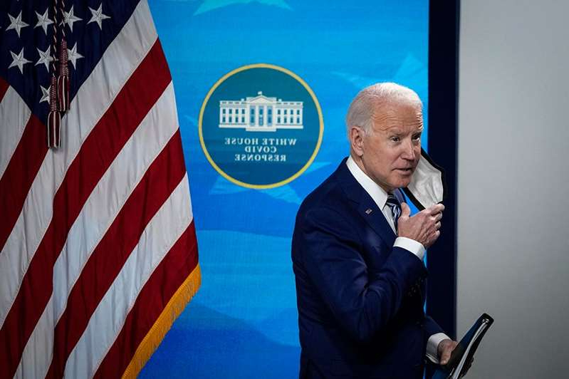 Joe Biden wearing a suit and tie talking on a cell phone: Biden targets corporations, averts political flashpoints in tax proposal