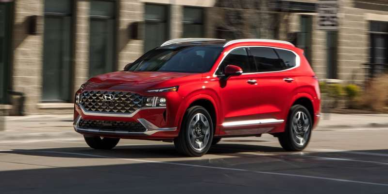 a car driving on a city street: In top Calligraphy trim, Hyundai's new Santa Fe two-row crossover has luxury aspirations and a strong, 277-hp turbo engine.