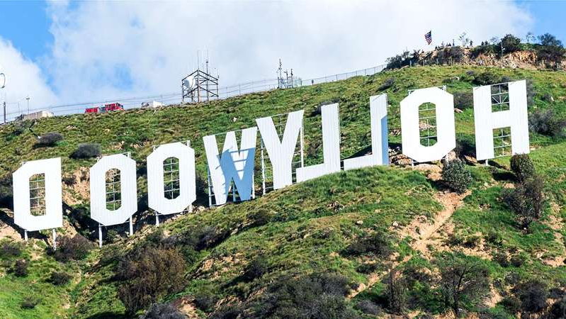 Hollywood Sign that has a sign on a grassy hill