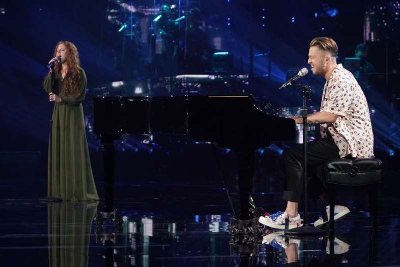a man standing on a stage: Cassandra Coleman and Ryan Tedder
