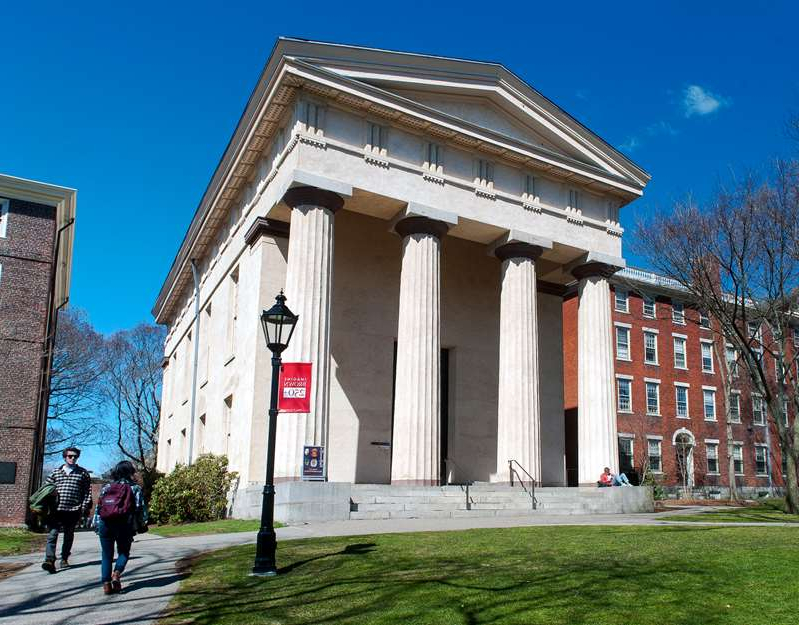 a group of people walking in front of a building: Brown is one of several universities to introduce a vaccine mandate. Pictured: Anthropology Museum of Brown University in April 2015.