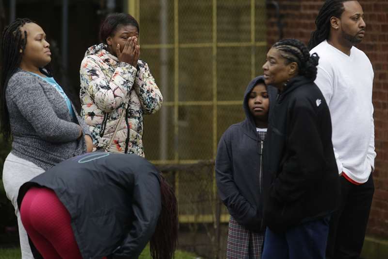 a group of people looking at a phone: People grieve after a shooting that left four people dead at a restaurant in the 2700 block of East 75th Street in Chicago, Illinois.