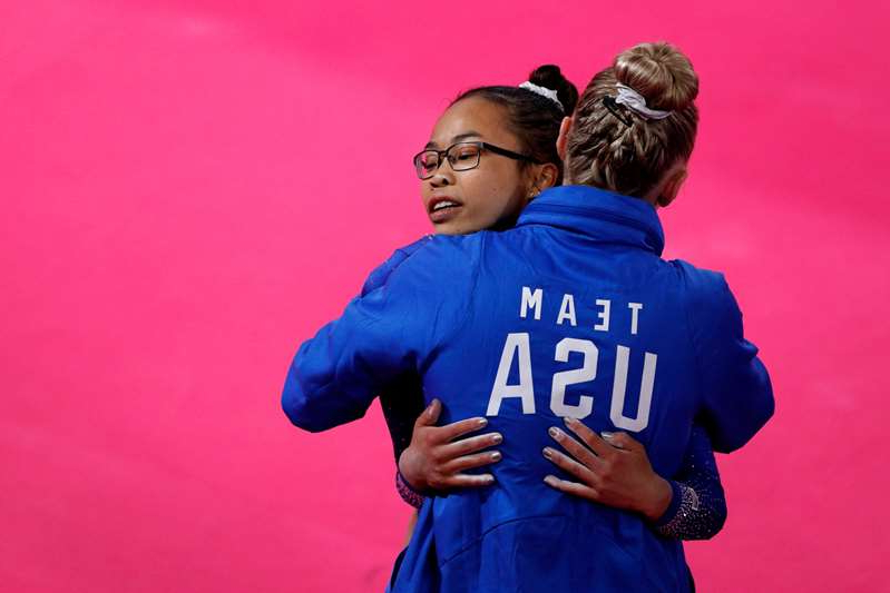 a man wearing a blue shirt: Morgan Hurd of the U.S. gets a hug from a coach after competing on floor in the women's gymnastics qualification and team final at the Pan American Games in Lima, Peru, Saturday, July 27, 2019.