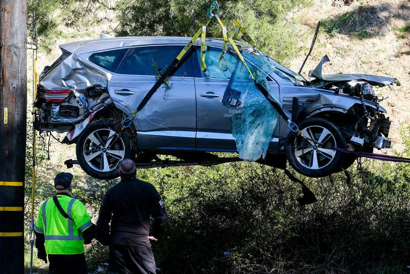 a motorcycle parked in front of a car: A crane lifts a vehicle after a rollover accident involving golfer Tiger Woods on Feb. 23 in the Rancho Palos Verdes section of Los Angeles.
